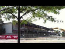 Excavators pulling down steel building